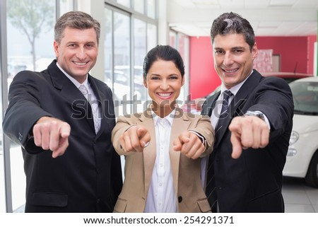 Smiling business team pointing at camera at new car showroom - stock photo