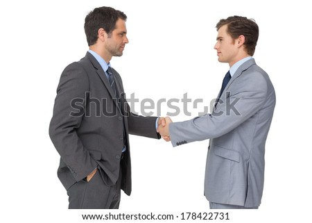 Smiling business team shaking hands on white background - stock photo