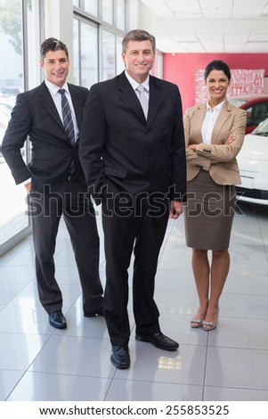 Smiling business team standing together at new car showroom - stock photo