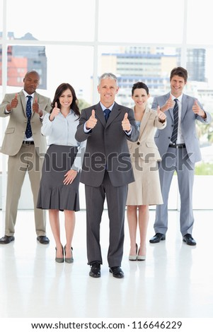 Smiling business team standing together with their thumbs up in success - stock photo