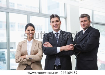 Smiling business team standing with arms crossed at new car showroom - stock photo
