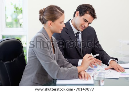 Smiling business team studying statistics in a meeting room - stock photo
