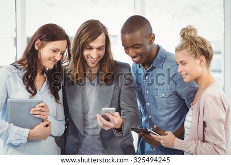 Smiling business team using technology while standing at office
