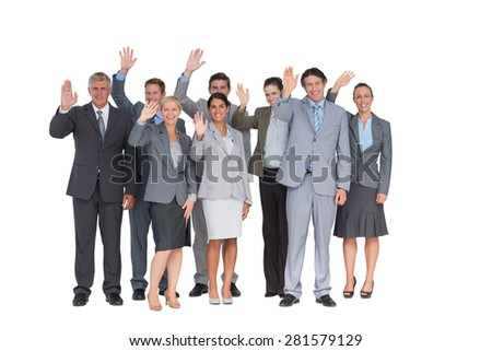 Smiling business team waving at camera on white background