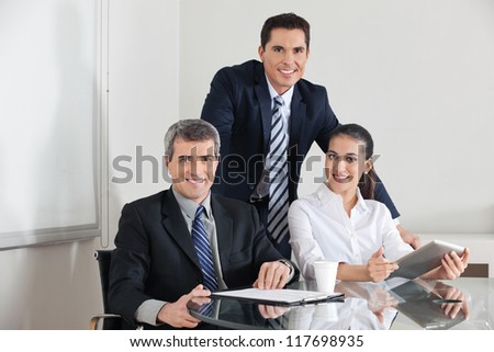 Smiling business team with laptop computer and clipboard in the office - stock photo