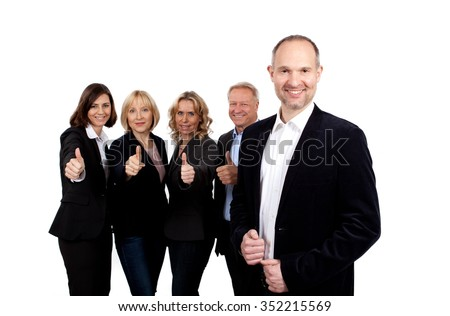 Smiling business team with manager in the front showing thumb up