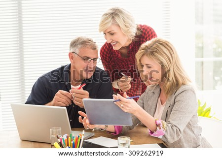 Smiling business team working over a tablet at office