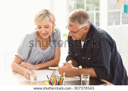 Smiling business team working together at the office - stock photo