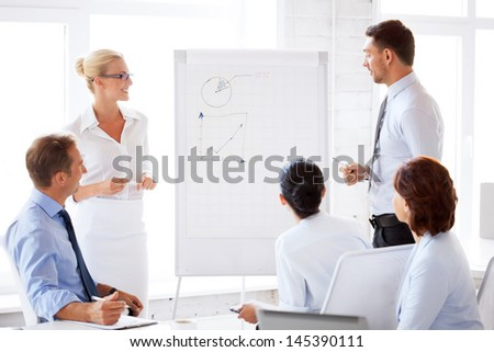 smiling business team working with flip chart in office - stock photo