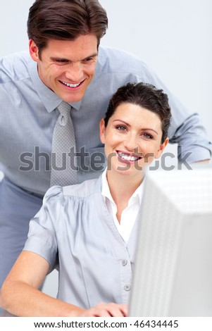 Smiling business woman and her colleague working at a computer in the office