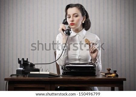 Smiling business woman eating a cookie, break from work - stock photo