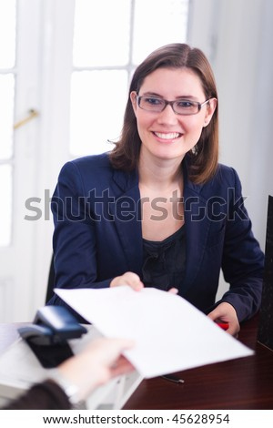 Smiling business woman handing contract to a colleague. - stock photo
