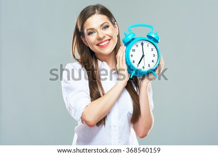 Smiling business woman hold alarm clock. Isolated portrait of young woman with long hair. Isolated.
