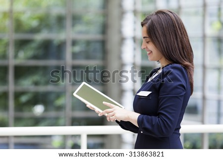 Smiling business woman holding a tablet computer at the office - stock photo