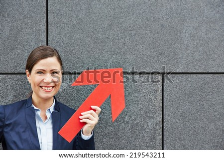 Smiling business woman holding big red arrow up - stock photo