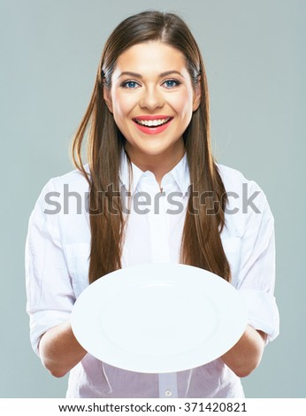 Smiling Business woman  holding empty white plate in front. Studio isolated portrait of young business woman. - stock photo