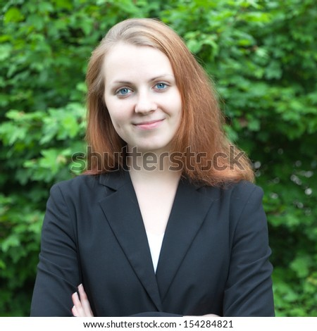Smiling business woman in a park
