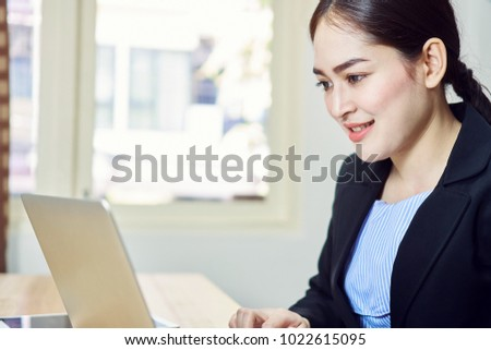 Smiling business woman in black suit is sitting working on laptop in office. Happy work concept.