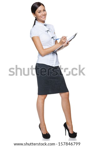Smiling business woman in full length making notes, isolated on white background