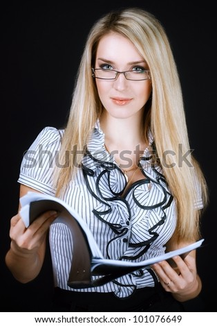 smiling business woman in glasses holding folder on black background - stock photo