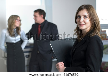 Smiling business woman in office at her collegues background