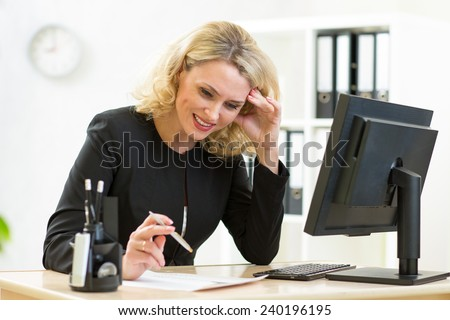 smiling business woman looks at document sitting at working place in office - stock photo