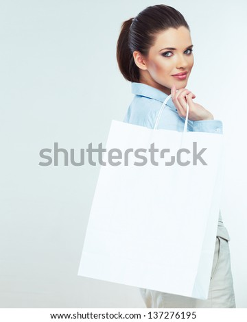 Smiling business woman looks out over white shopping bag. Isolated female portrait. Girl model - stock photo