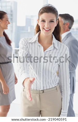 Smiling business woman offering handshake at work - stock photo