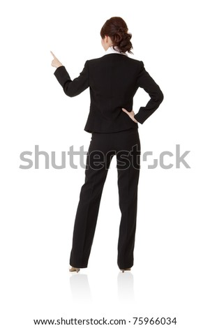 Smiling business woman pointing and presenting, rear view full length portrait isolated on white background.