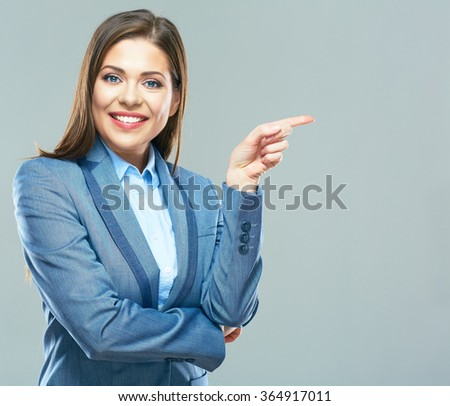 Smiling business woman  pointing finger on copy space. Business style suit. Young model with long hair. - stock photo