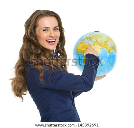 Smiling business woman pointing in earth globe