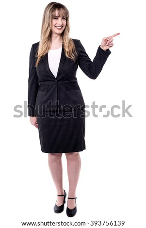 Smiling business woman pointing to copy space - stock photo