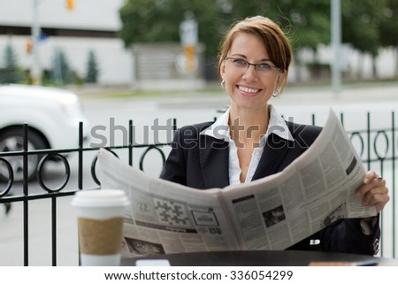 Smiling business woman reads newspaper at outdoor coffee shop - stock photo