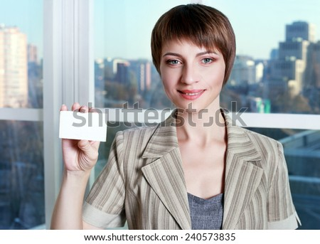 smiling business woman showing blank credit card over city view background - stock photo