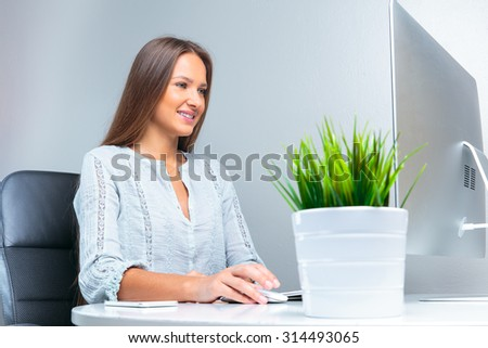 smiling business woman siting at the office - stock photo