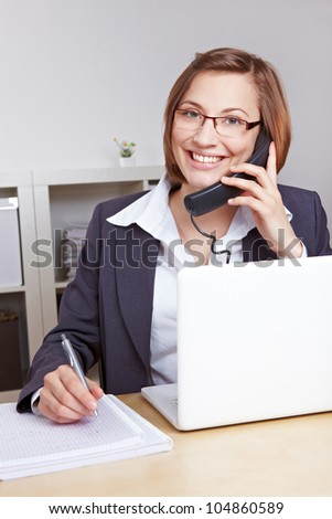 Smiling business woman sitting at her desk in the office talking on the phone - stock photo