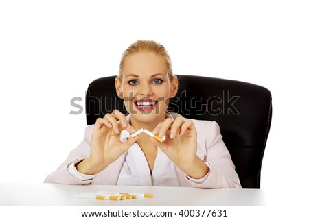 Smiling business woman sitting behind the desk and breaking cigarette