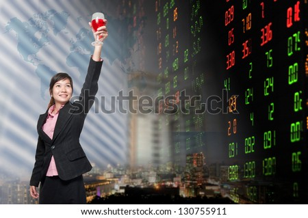 Smiling business woman standing holding a glass of champagne. over stock exchange background - stock photo