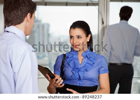 Smiling business woman standing with her colleague in office - stock photo