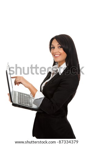 Smiling business woman standing with laptop point finger on screen. Isolated over white background