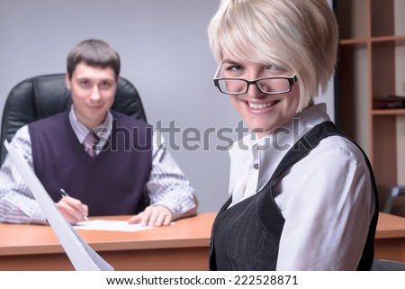 Smiling business woman studies document over colleague background in office - stock photo