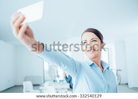 Smiling business woman taking a selfie in her office using a smart phone - stock photo