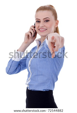 Smiling business woman talking on mobile phone and pointing finger at you - stock photo