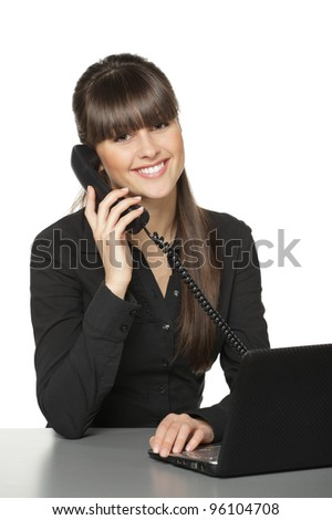 Smiling business woman talking on the phone at her work desk, isolated on white background