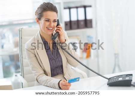 Smiling business woman talking phone in office - stock photo