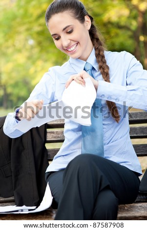 smiling business woman terminates the contract ripping, outdoor - stock photo