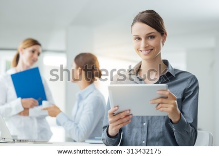Smiling business woman using a digital tablet and female office workers talking on background - stock photo