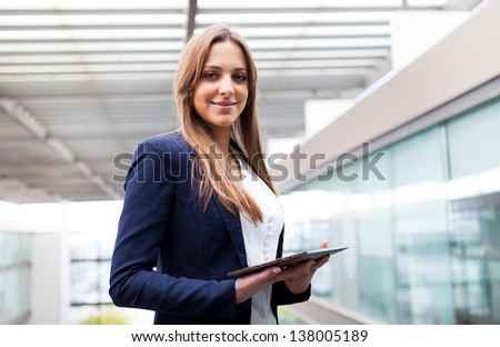 Smiling business woman using a tablet PC at the office - stock photo