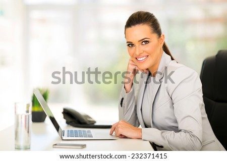 smiling business woman using laptop computer - stock photo