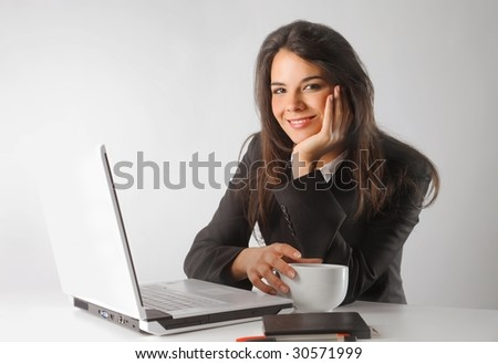 smiling business woman with cup of coffee and laptop